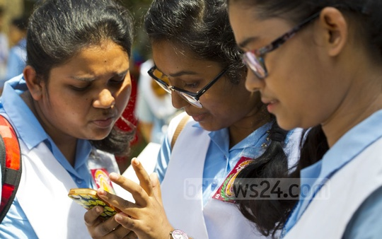 Students checking their HSC exam results on mobile phones at Viqarunnisa Noon School and College in Dhaka on Thursday. Photo: Mostafigur Rahman