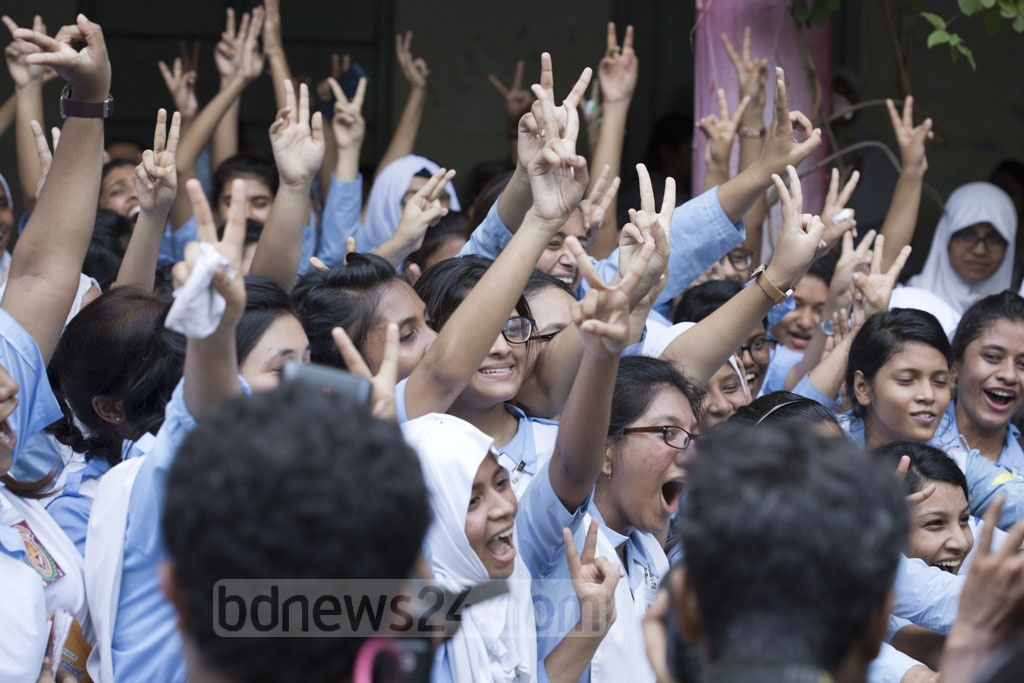 Students flash victory sign after publication of HSC exam results at Viqarunnisa Noon School and College in Dhaka on Thursday. Photo: Mostafigur Rahman