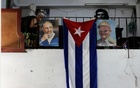 The Cuban flag hangs next to the photographs of late Cuba's President Fidel Castro and his brother, Cuba's former President Raul Castro, in Havana, Cuba Jul 21, 2018. Reuters