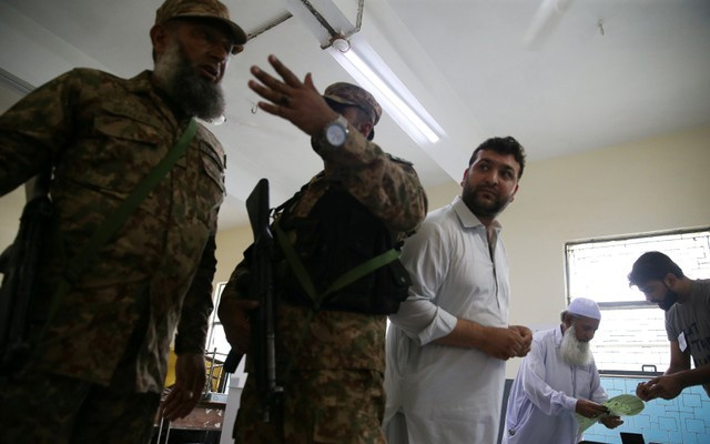 Soldiers discuss as voters cast their votes at a polling station during general election in Islamabad, Pakistan, July 25, 2018. REUTERS/Athit Perawongmetha