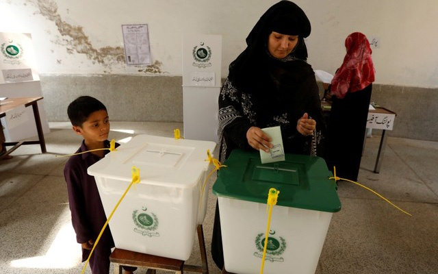 A child watches his mother casts her ballot at a polling station during general election in Rawalpindi, Pakistan July 25, 2018. REUTERS/Faisal Mahmood