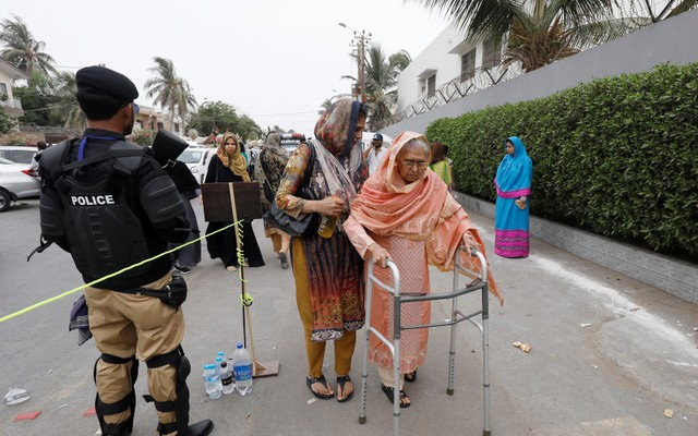 A voter walks next to a police officer as she prepares to cast her vote during the general election in Karachi, Pakistan, July 25, 2018. REUTERS/Akhtar Soomro
