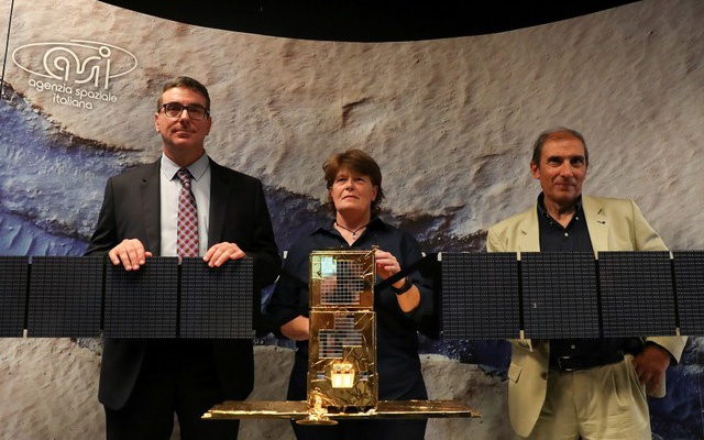 Scientists Roberto Orosei (L), Elena Pettinelli (C) and Enrico Flamini pose near a replica of the Cosmo Sky Med satellite before a news conference where they announce the first-time detection of liquid water on Mars by Italian radar MARSIS, on board the ESA's Mars at the Italian Space Agency headquarters in Rome, Italy July 25, 2018. Reuters