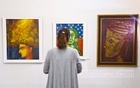 A visitor looks at a painting at the 14th Anniversary Exhibition of Galleri Kaya on Friday.