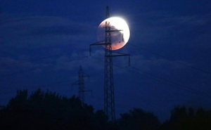 A full moon during an eclipse rises behind power line in Zenica, Bosnia and Herzegovina, Jul 27, 2018. Reuters