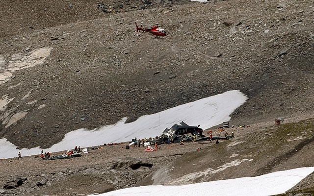 A helicopter is seen above the accident site of a Junkers Ju-52 airplane of the local airline JU-AIR that is 2,450 meters above sea level near the mountain resort of Flims Switzerland Aug 5 2018. Reuters