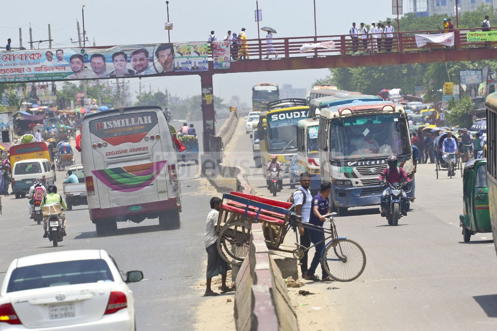A man pulling his rickshaw-van over a road-divider at Shanir Akhra on Tuesday. Photo: Abdullah Al Momin