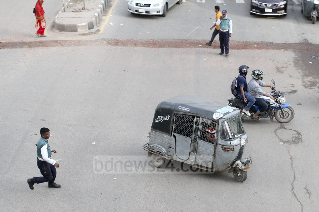 A policeman chasing an autorickshaw driver who tried to dodge one of the checkposts installed on Dhaka streets during the Traffic Week to check papers of vehicles at Banglamotor on Wednesday.