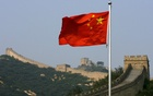 A Chinese flag flies in front of the Great Wall of China, located north of Beijing. Reuters