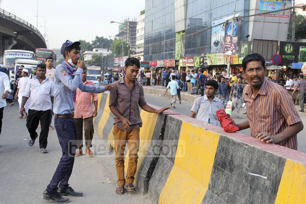 Members of Bangladesh Scouts asking jaywalkers at Dhaka's Mohakhali on Thursday to use footbridge and other safe means to cross streets as part of a campaign to raise awareness about traffic rules. Photo: Asif Mahmud Ove