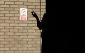 A woman smokes in the shadows outside Southwark Crown Court in central London, Mar 5, 2014. REUTERS