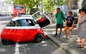Chief Marketing Officer Merlin Ouboter (L) of Swiss Microlino AG sits in an electric-powered Microlino car as he answers questions of tourists from the United States in Zurich, Switzerland August 16, 2018. Reuters