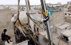 FILE PHOTO: A sacrificial cow is lowered from a rooftop by crane, ahead of the Eid-ul-Azha festival in Karachi, Pakistan, August 12, 2018. Reuters