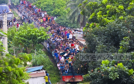 People risk their lives by travelling to Dhaka from Narayanganj on the roof of a crammed train. This photo was taken from Sayedabad on Monday.
