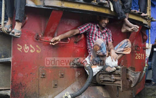 A desperate man travelling on the engine connector of a train at Airport Railway Station in Dhaka on Tuesday.