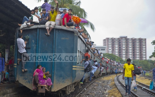 Two women travelling on a coach connector of a train. This photo was taken from Airport Railway Station in Dhaka on Tuesday.