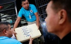 Thai police officers unload seized drugs from a vehicle in a police station in Bangkok, Thailand August 22, 2018. Reuters