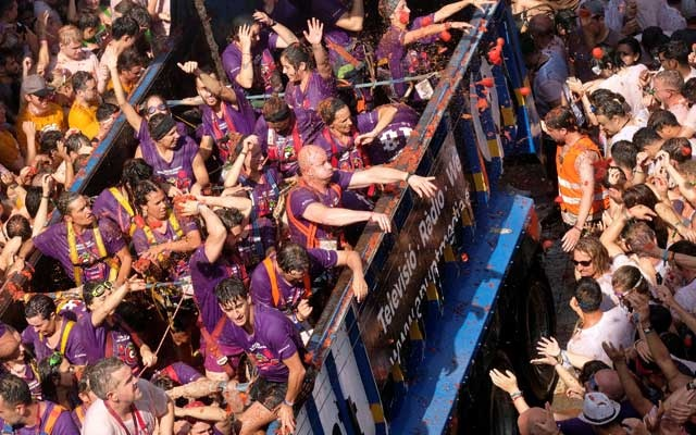 Revellers on a truck throw tomatoes into the crowd during the annual
