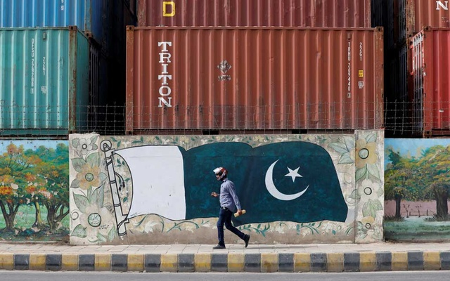 A man walks past a wall of a shipping container's yard painted with a national flag ahead of Pakistan's Independence Day, in Karachi, Pakistan Aug 6, 2018. Reuters