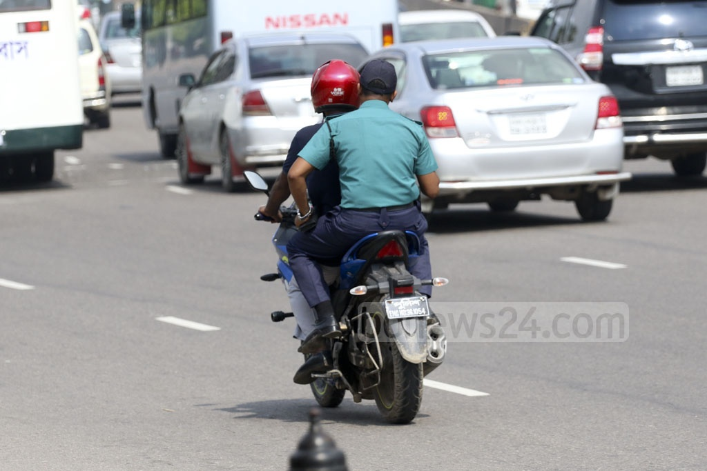 A policeman travelling on a motorcycle without helmet amidst strengthened monitoring by the law enforcers in Dhaka. This photo was taken from the Airport Road on Monday. Photo: Abdullah Al Momin