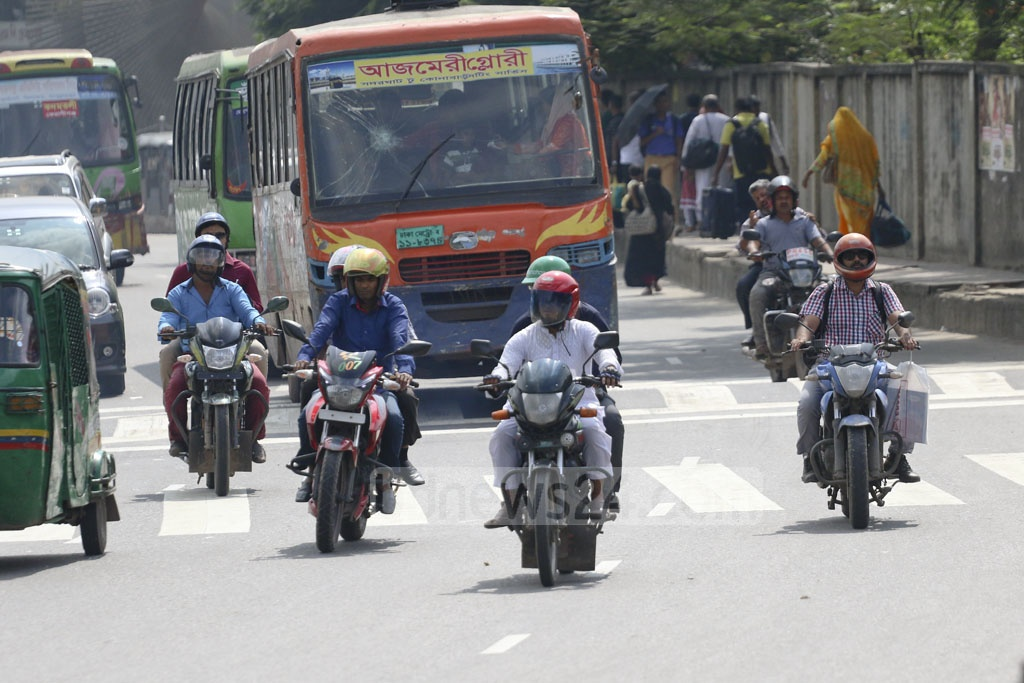 Motorcycle riders wearing helmets travel in Dhaka on Monday amidst strengthened monitoring by the law enforcers. This photo was taken from the Airport Road. Photo: Abdullah Al Momin