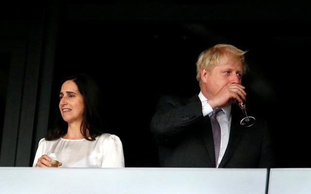 FILE PHOTO: London mayor Boris Johnson (R) sips wine as his wife Marina Wheeler stands to his left in the VIP box before the opening ceremony of the London 2012 Olympic Games at the Olympic Stadium July 27, 2012. Reuters