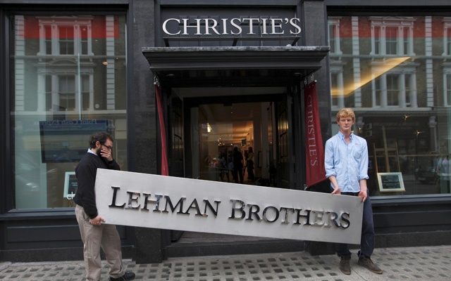 Christie's employees pose with a Lehman Brothers sign at Christie's in central London Sep 24, 2010. REUTERS