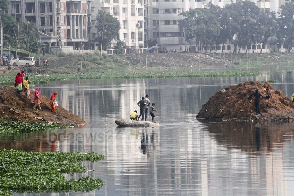 A dam was built for digging Dhaka's Gulshan Lake a few days ago. After the digging ended, the dam was demolished. In the meantime, Korail slum dwellers got used to walking through the dam and they now cross the Lake on a raft made of plastic bottles. The photo was taken on Thursday. Photo: Asif Mahmud Ove
