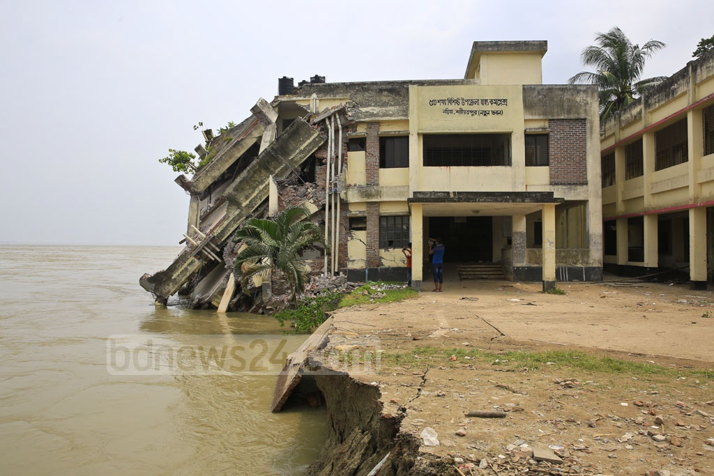 The new Naria Upazila Health Complex building topples as the Padma erodes the soil underneath. Photo: Mostafigur Rahman