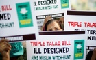 Muslim women hold placards during a protest against a bill passed by India's lower house of Parliament last week that aims at prosecuting Muslim men who divorce their wives through the
