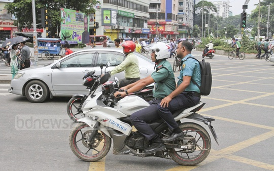 Both motorbike drivers and pillion riders have to wear helmets under the traffic rules. Here is a case in which police themselves ignore the rules in Dhaka's Gulshan. Photo: Asif Mahmud Ove
