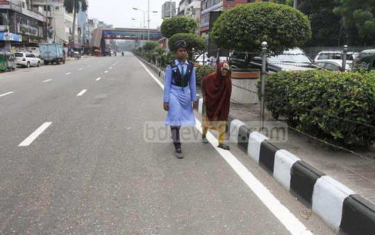 A member of Bangladesh Scouts helping an elderly woman cross the Bijoy Soroni road in Dhaka on Friday. Photo: Asif Mahmud Ove