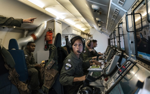 Lt Deanna Coughlin, centre, monitors a feed from an onboard camera on a US Navy P-8A Poseidon reconnaissance plane during a mission to observe China's militarisation of islands in the South China Sea, in International Airspace, Sept. 5, 2018. The flight brings harsh Chinese challenges in officially international space. In congressional testimony by one officer, China is said to be capable of control over the South China Sea