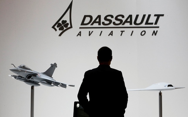 File Photo: A visitor looks at replicas of the fighter jet Rafale (L) and Neuron on the Dassault booth during the European Business Aviation Convention & Exhibition (EBACE) at Cointrin airport in Geneva, Switzerland, May 19, 2015. Reuters