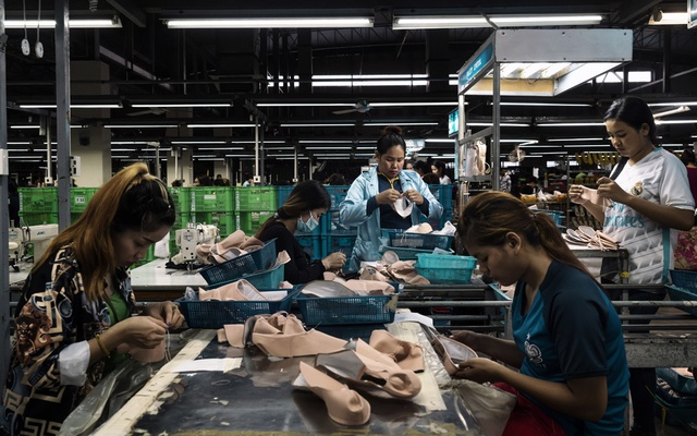 Workers at a factory that makes Bloch ballet shoes cut leather from Brazil, apply glue and pinch, gather and hammer the material into soles, in Phnom Penh, Cambodia, Sept. 13, 2018. Companies are reconsidering where to put their factories as the trade war between the United States and China mounts, but few places can match China's convenience and reliability. (Adam Dean/The New York Times)
