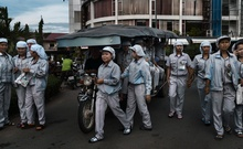 Factory workers at the end of their shift in Phnom Penh, Cambodia, July 27, 2018. Companies are reconsidering where to put their factories as the trade war between the United States and China mounts, but few places can match China's convenience and reliability. (Adam Dean/The New York Times)