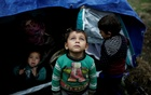 A Syrian refugee boy stands in front of his family tent at a makeshift camp for refugees and migrants next to the Moria camp on the island of Lesbos, Greece, Nov 30, 2017. REUTERS