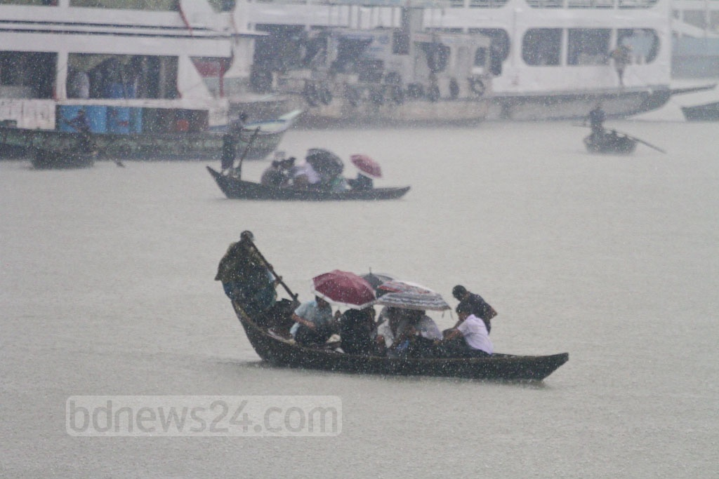 Working people are crossing the Burhiganga River in Dhaka on boat holding umbrellas during rains on Thursday after a spell of heat. Photo: Asif Mahmud Ove