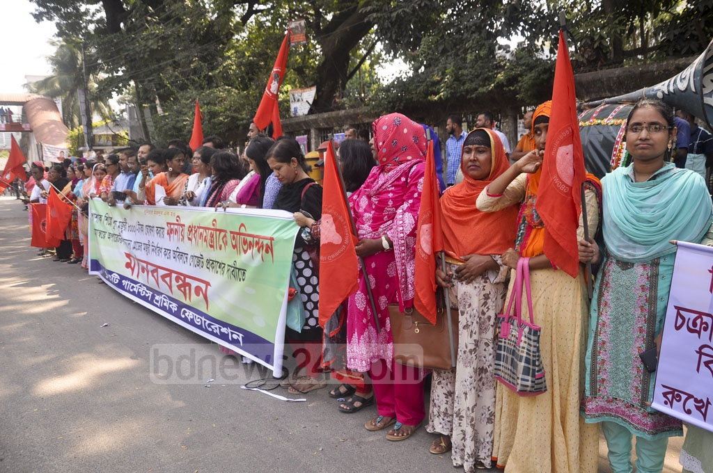 Thirteen organisations of garment workers hold a human chain in front of the National Press Club in Dhaka, demanding Tk 8,000 as the monthly minimum wage on Tuesday.