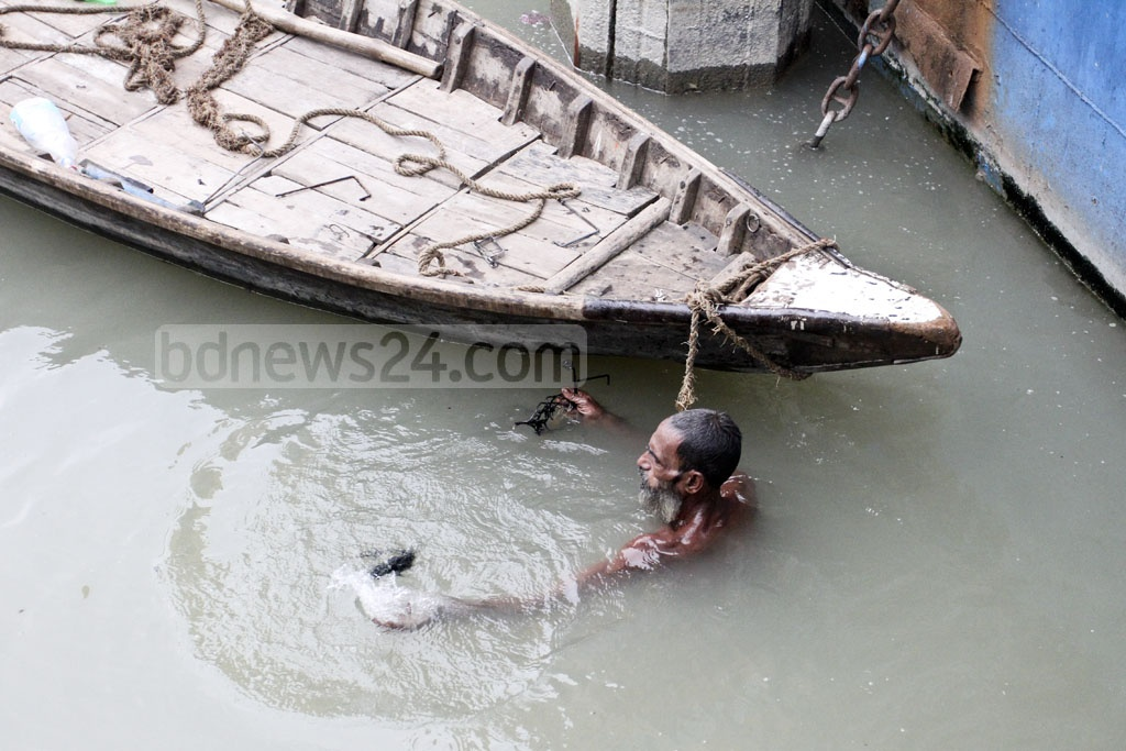 Montu Mia earns a living by diving for metals objects in the Buriganga River and selling them. Photo: Asif Mahmud Ove