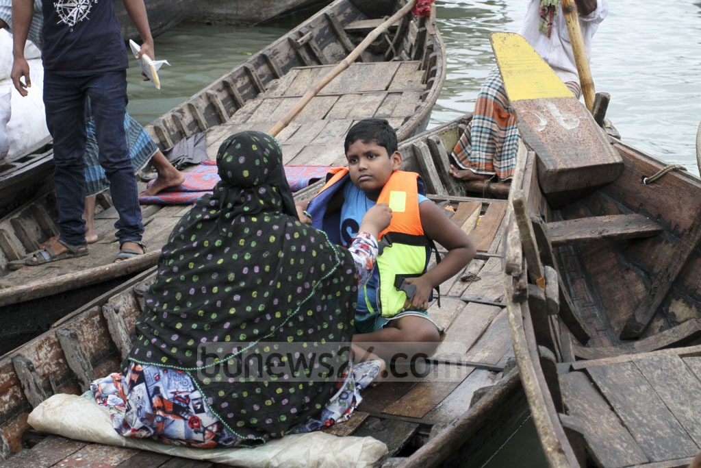 A woman takes her son to school by boat on Saturday. The two Keraniganj residents cross the Buriganga River every day, with the child in lifejacket, for his school and coaching in Old Dhaka. Photo: Asif Mahmud Ove