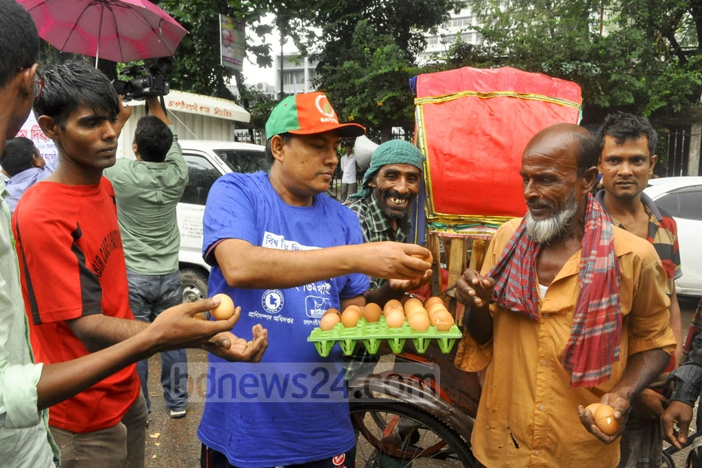 Eggs are distributed for free among the poor in front of the National Press Club on Friday to mark World Egg Day.
