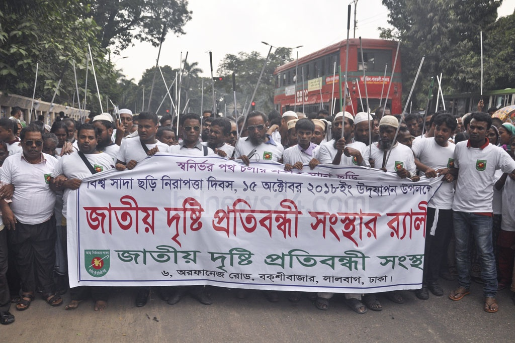 An organisation for people with visual disabilities holds a procession in front of the National Press Club in Dhaka on Monday to mark White Cane Safety Day.