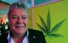 Aphria CEO Vic Neufeld poses near a wall covering of a marijuana leaf at a party the day before Canada's legalisation of recreational cannabis in Toronto, Ontario, Canada Oct 16, 2018. Reuters