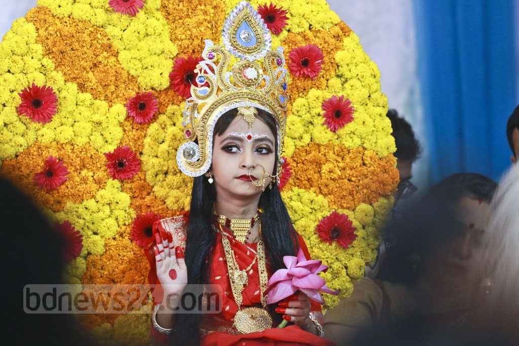 A child symbolising the living image of the goddess Durga receives prayers at Dhaka's Ramkrishna Mission on Wednesday, the Durga Puja Maha Ashtami. Photo: Abdullah Al Momin