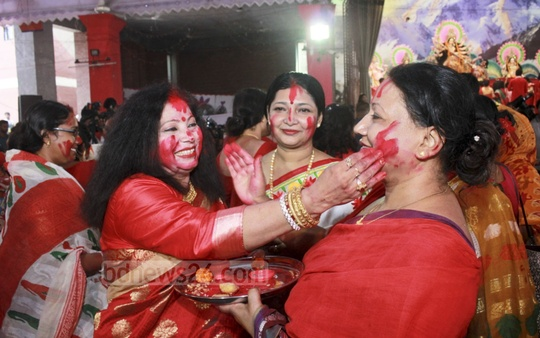 Hindu devotees marking each other with sindoor or vermillion at the Dhakeshwari National Temple in Dhaka on Friday as they prepare to bid adieu to the goddess Durga for immersion in the river on Maha Dashami.