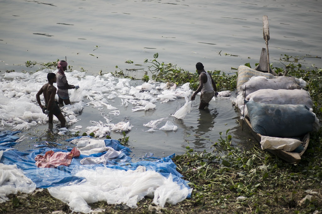 Labourers wash polythene bags, which were used to carry chemicals, in the Buriganga river for recycling at Kamrangirchar in Dhaka on Friday. Photo: Mostafigur Rahman