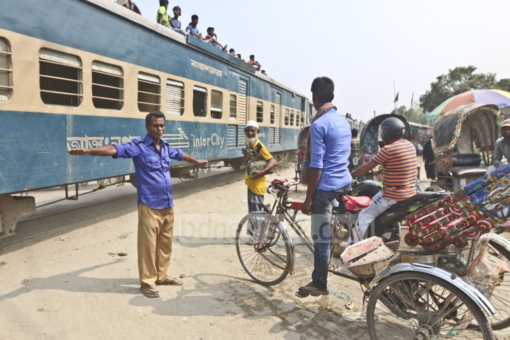 As there is no barrier at the Barhaitala level-crossing in Dhaka, the gatekeeper stands spreading his hands to stop vehicles while a train is passing by on Thursday. Photo: Abdullah Al Momin