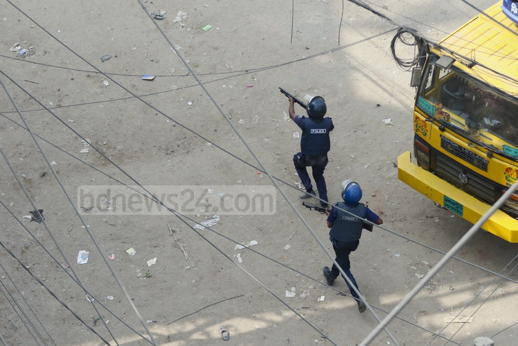 Armed police members chase away protesting transport workers. Photo: Abdullah Al Momin