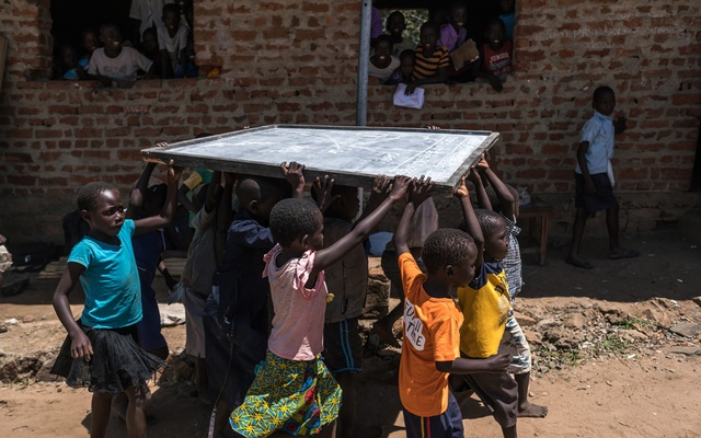 Students carry a blackboard outside Imvepi Primary School in Imvepi, Uganda, Oct 17, 2018. The New York Times